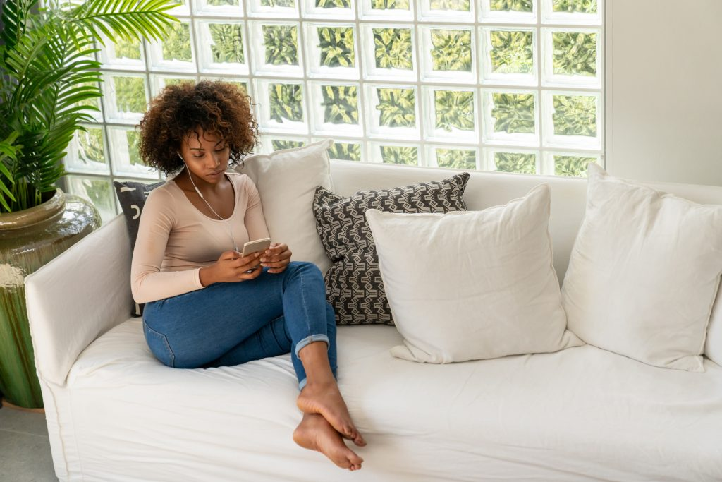 Woman listening to Hallow on her couch